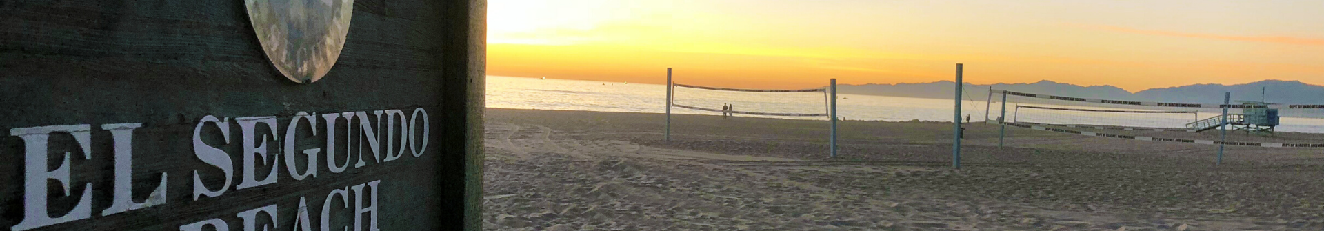 El Segundo Beach sign at sunset with volleyball nets