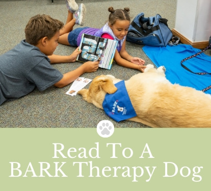 Children reading to therapy dog